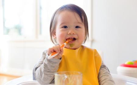 Photo pour Happy little baby boy eating food in his house - image libre de droit