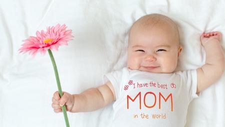 Foto de Mothers Day message with baby girl holding a flower - Imagen libre de derechos