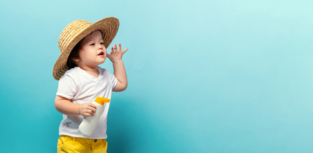 Photo pour Toddler boy with a bottle of sunblock on a blue background - image libre de droit