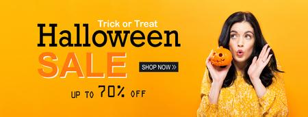 Photo pour Halloween sale with young woman holding a pumpkin - image libre de droit