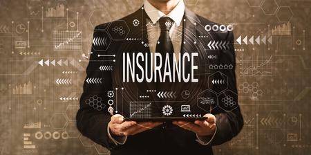 Photo pour Insurance with businessman holding a tablet computer on a dark vintage background - image libre de droit