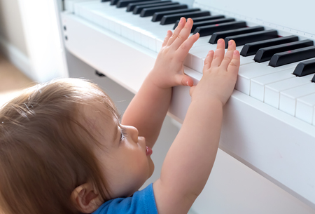 Foto de Toddler boy excited to reach up and play the piano - Imagen libre de derechos