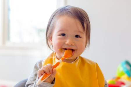 Photo pour Happy toddler boy smiling while eating a meal - image libre de droit
