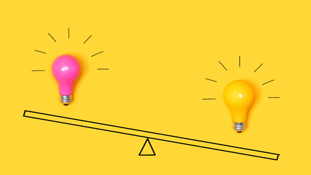 Photo for Idea light bulbs on a scale on a yellow background - Royalty Free Image