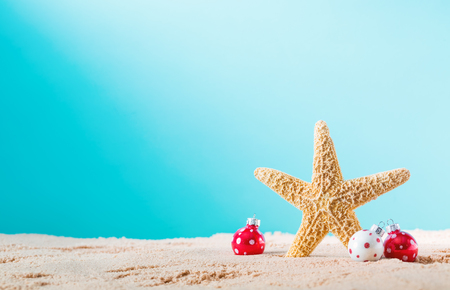 Foto de Starfish with Christmas ornaments on a beach sand - Imagen libre de derechos