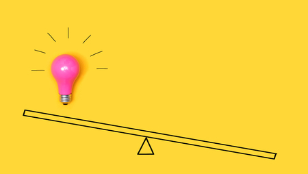 Photo for Idea light bulb on a scale on a yellow background - Royalty Free Image