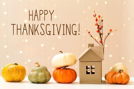 Photo pour Thanksgiving message with collection of autumn pumpkins with a toy house - image libre de droit