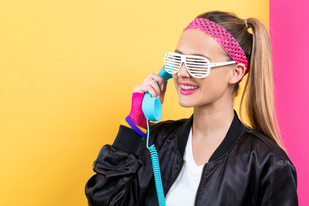 Foto de Woman in 1980s fashion with old fashioned phone on a split yellow and pink background - Imagen libre de derechos