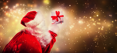 Photo for Santa holding a Christmas gift on a shiny light background - Royalty Free Image