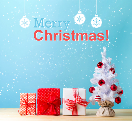 Photo for Merry christmas message with a white Christmas tree and gift boxes - Royalty Free Image