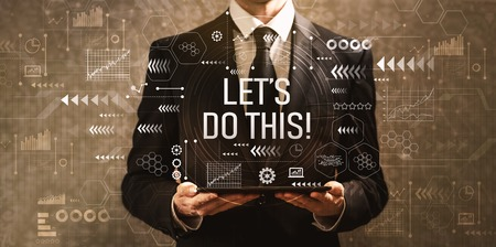 Lets do this with businessman holding a tablet computer on a dark vintage background