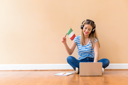 Photo pour Young woman with Italian flag using a laptop computer against a big interior wall - image libre de droit