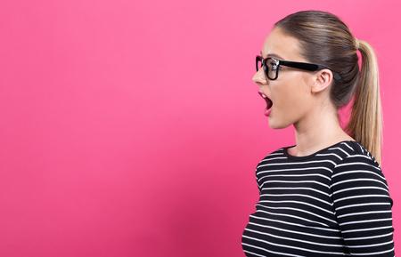Photo pour Young woman talking on a pink background - image libre de droit