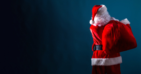 Foto de Santa holding a red sack on a dark blue background - Imagen libre de derechos