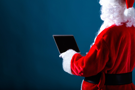 Foto de Santa using a laptop on a dark blue background - Imagen libre de derechos