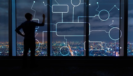 Photo for Flowchart with man writing on large windows high above a sprawling city at night - Royalty Free Image