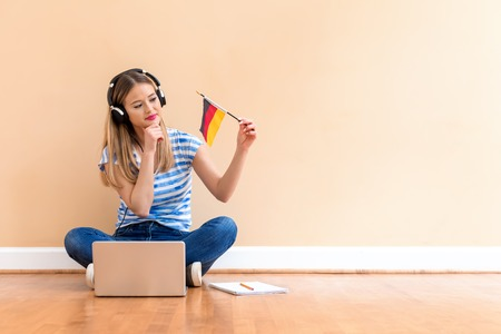 Photo pour Young woman with Germany flag using a laptop computer against a big interior wall - image libre de droit