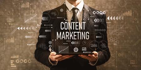 Photo pour Content marketing with businessman holding a tablet computer on a dark vintage background - image libre de droit