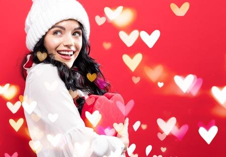 Foto de Happy young woman holding a big heart gift box with heart lighs - Imagen libre de derechos