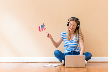 Photo pour Young woman with USA flag using a laptop computer against a big interior wall - image libre de droit