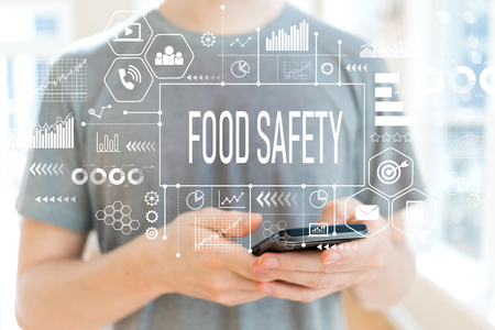 Photo pour Food safety with young man using a smartphone - image libre de droit