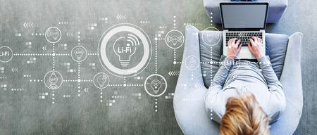 Photo pour LiFi theme with man using a laptop in a modern gray chair - image libre de droit