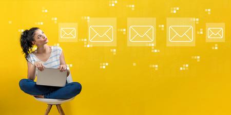 Photo pour Emails with young woman using a laptop computer - image libre de droit