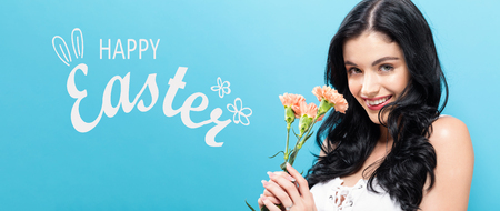 Photo for Happy Easter message with young woman holding carnation flowers - Royalty Free Image