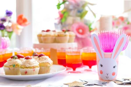 Photo pour Dessert table with cupcakes and flowers Easter party theme - image libre de droit