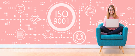 Photo pour ISO 9001 with young woman using her laptop in a chair - image libre de droit