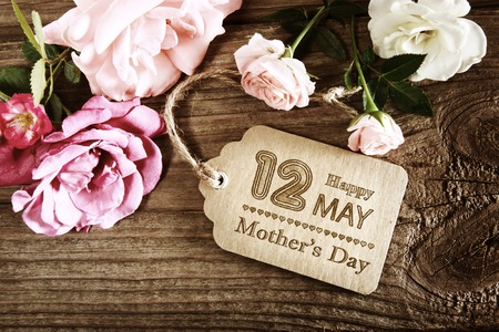 Photo pour Mothers Day message with small pink roses on wooden table - image libre de droit