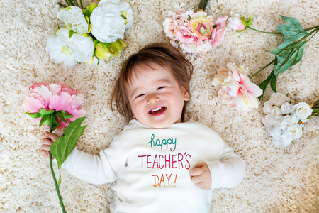 Photo pour Teachers Day message with happy toddler boy with spring flowers - image libre de droit