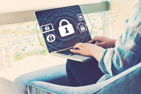Foto de Security theme with woman using her laptop in her home office - Imagen libre de derechos