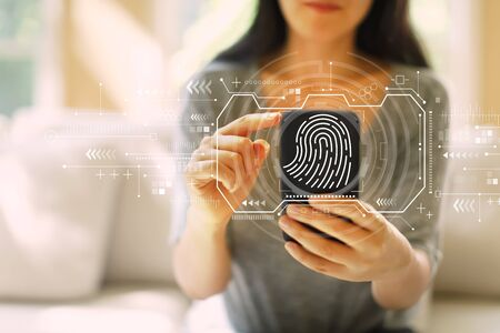 Photo pour Fingerprint scanning theme with woman using her smartphone in a living room - image libre de droit
