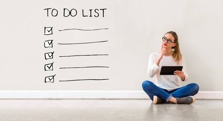 Photo pour To do list with young woman holding a tablet computer - image libre de droit