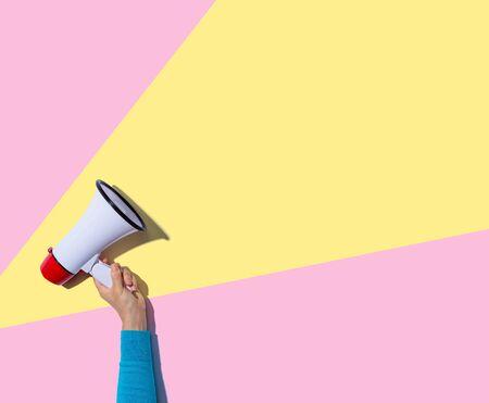 Photo pour Person holding a megaphone with hard shadow - image libre de droit