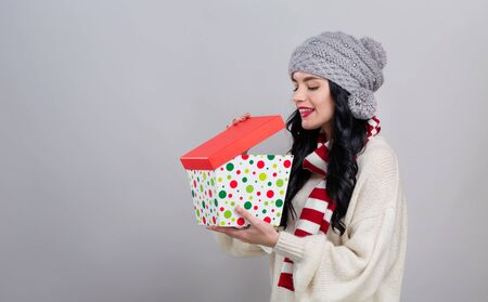 Photo for Young woman opening a Christmas present box on a gray background - Royalty Free Image
