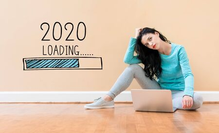 Foto de Loading new year 2020 with young woman using a laptop computer - Imagen libre de derechos