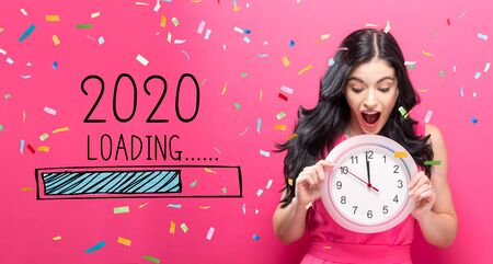 Foto de Loading new year 2020 with young woman holding a clock showing nearly 12 - Imagen libre de derechos