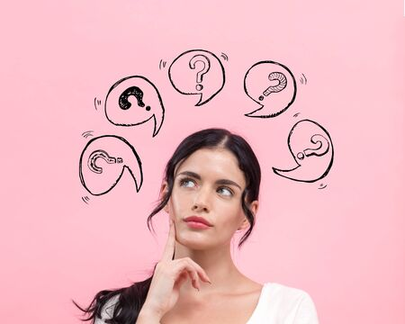Photo pour Question marks with speech bubbles with young woman in thoughtful pose - image libre de droit