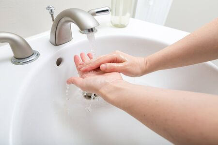 Photo pour Person washing their hands at with soap and water for coronavirus prevention - image libre de droit