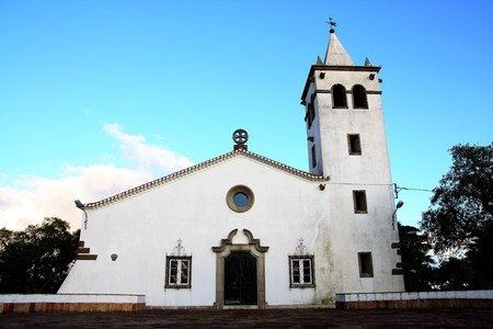 Full frontal view of a small christian church on the village of Barranco do Velho in Algarve, Portugal.