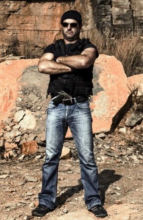 View of a man with a gun in jeans and jacket on a stone quarry.