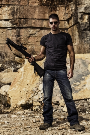 View of a man with a shotgun in jeans and black shirt on a stone quarry.