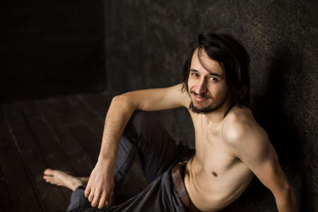 Foto de Skinny man without T-shirt sits looking at camera from below, beard mustache. - Imagen libre de derechos