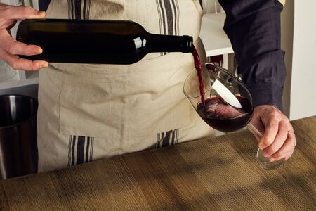 Foto de Man with an apron serving a glass of red wine - Imagen libre de derechos
