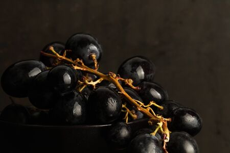Bunch of black grapes in a black ceramic bowl on a dark background