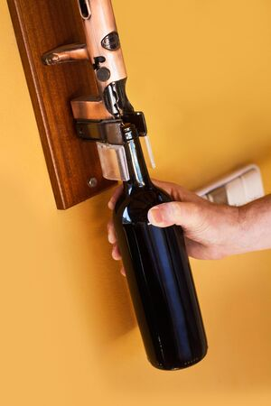 Man opening a bottle of red wine with a big metal corkscrew on a yellow wall