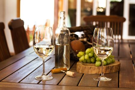 Two glasses and a bottle of white wine on a teak wood table