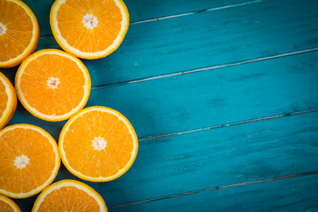 Fresh organic oranges halves  fruits on blue wooden background with copy space